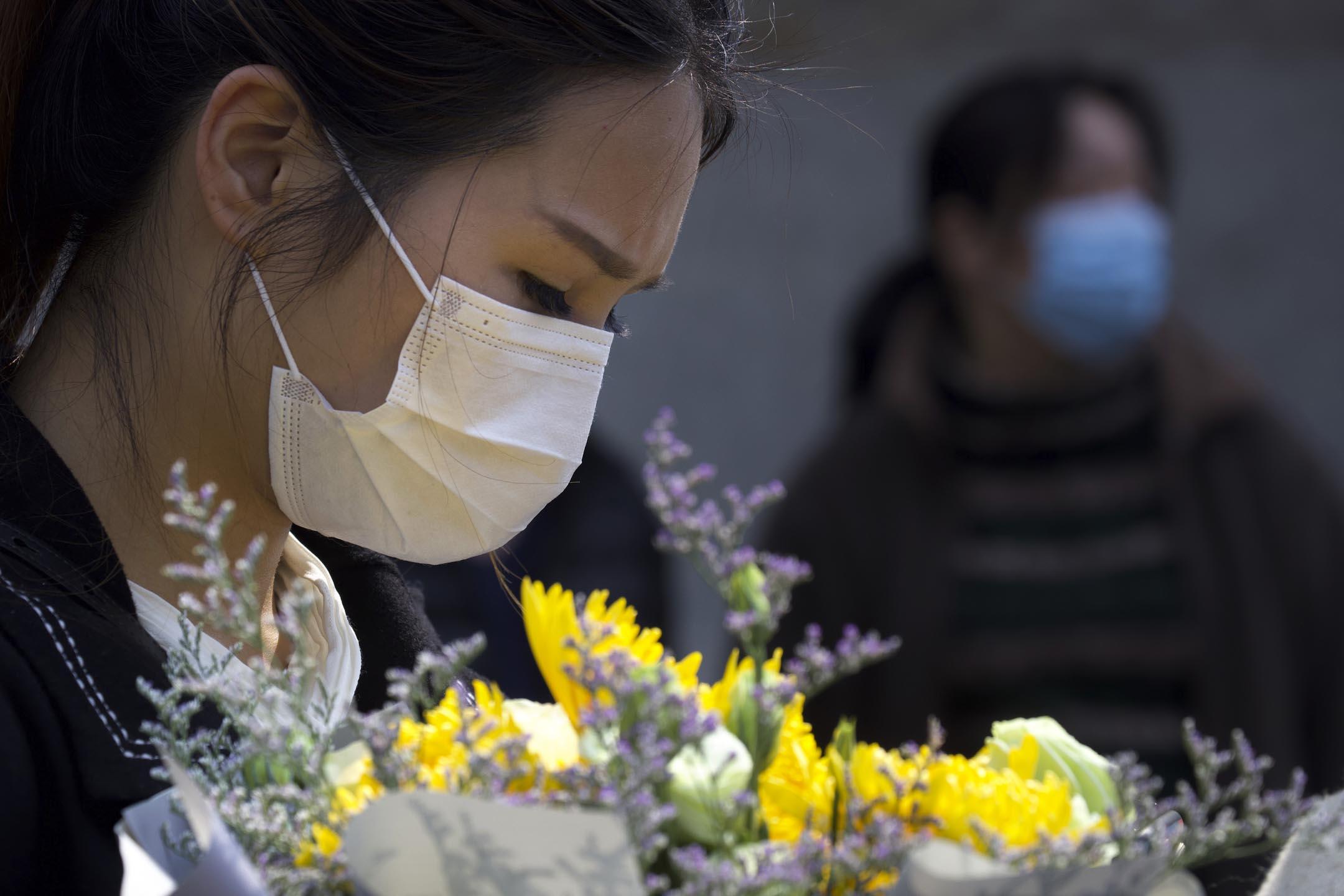 2020年4月4日,一名女士手持鮮花悼念2019冠狀病毒肺炎死者。 攝:Ng Han Guan/AP/達志影像