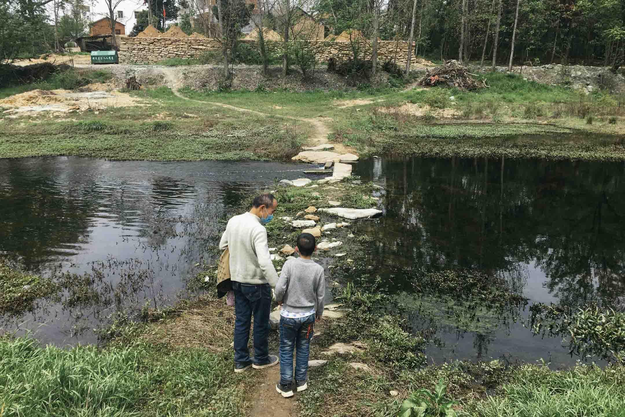鄢小文與小兒子宏偉在鄢家村的一條河流前。 攝影:白素