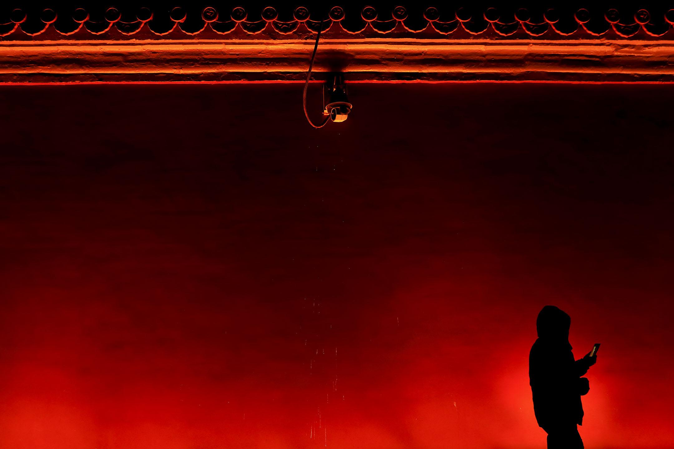 2018年1月31日,一名男子從中國北京故宮外拍下藍月亮後,在監控攝像機下走過。 攝:Damir Sagolj/Reuters/達志影像