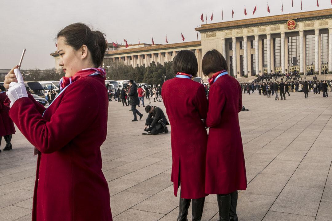 2018年3月5日,北京舉行的第十三屆全國人大第一次會議前,人民大會堂前有女士使用手機。