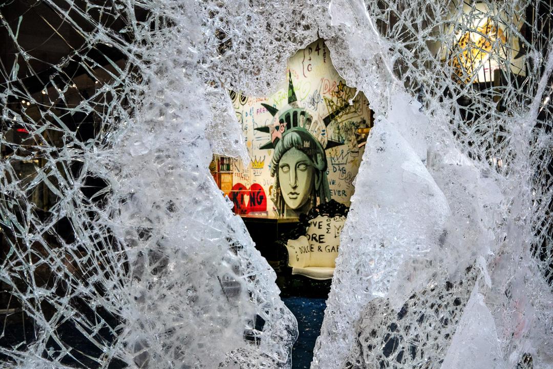 2020年6月1日,紐約一家商店的櫥窗被示威者打碎,店內掛著自由女神像的畫像。 攝:Mark Lennihan/ AP/ 達志影像