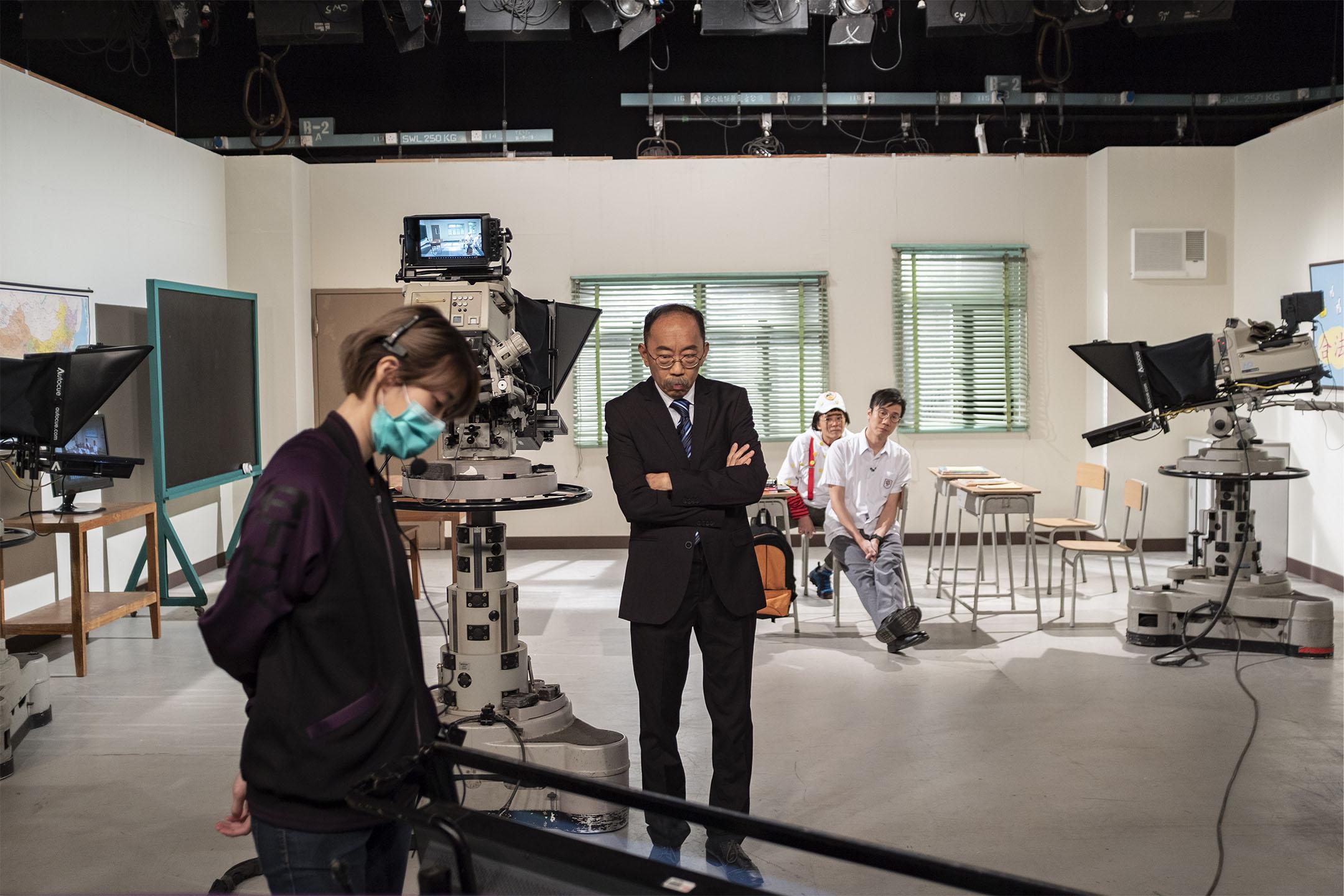 扮演校長的吳志森與扮演黃之鋒的曾志豪在觀看重播。