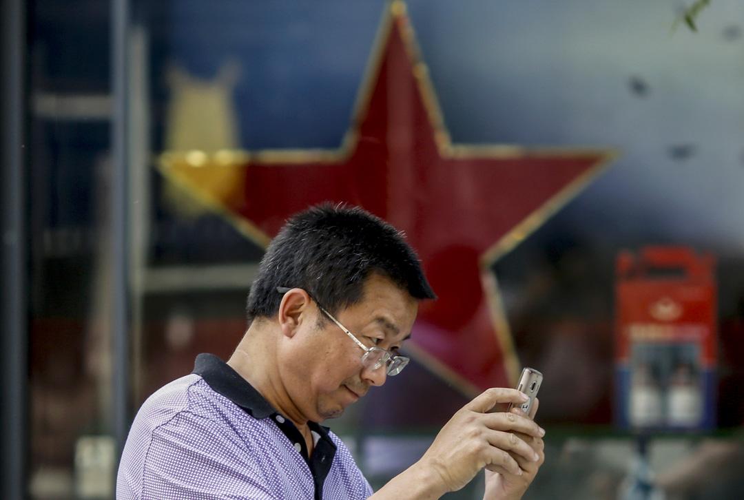 2016年5月20日,一名男子在北京一家零售店前使用手機。