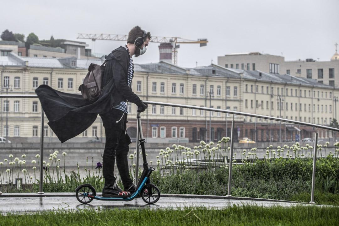 2020年6月2日,一名戴著口罩的男子在雨中騎著電單車在俄羅斯莫斯科的一條林蔭大道上行駛。 攝:Alexander Zemlianichenko Jr/AP/ 達志影像