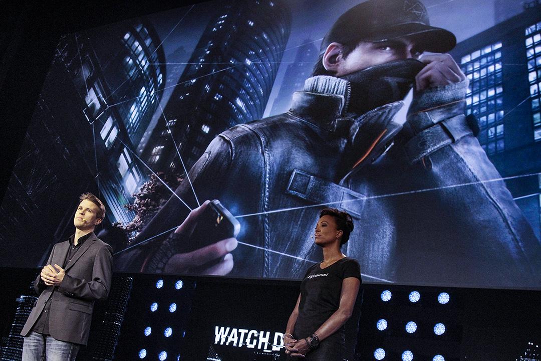 """2013年6月10日,Ubisoft的高級製作人多米尼克·瓜伊(Dominic Guay)和主持人艾莎·泰勒(Aisha Tyler)在美國加利福尼亞州洛杉磯舉行的Ubisoft SA E3媒體聚會上談論遊戲""""看門狗""""。 攝:Jonathan Alcorn/Bloomberg via Getty Images"""