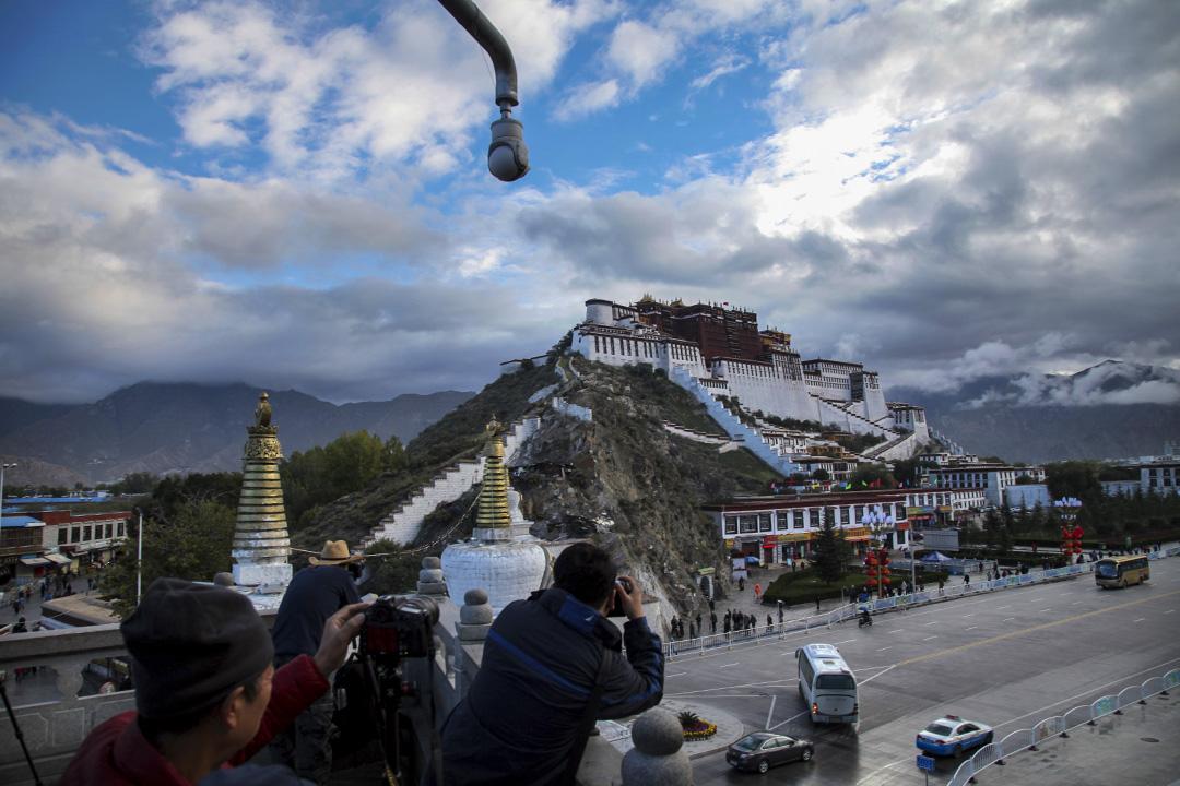 2015年9月19日,遊客在中國西藏自治區首府拉薩的安全攝像頭下拍攝布達拉宮。