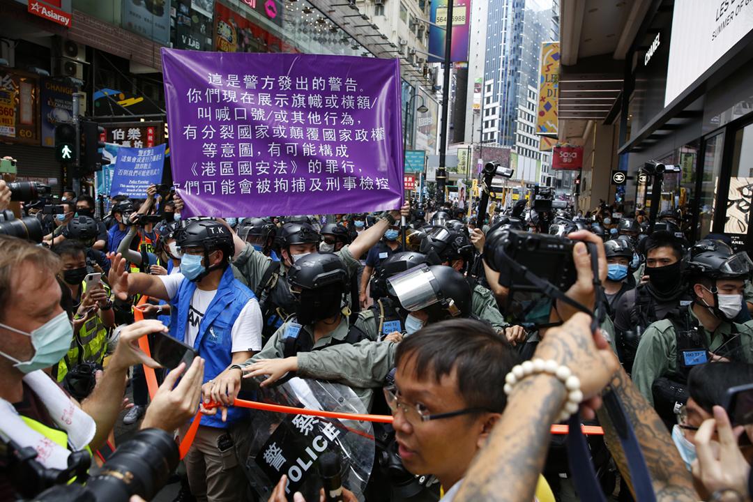 2020年7月1日,香港警方應對集結人群期間,首次舉起因應「港區國安法」而配備的紫色警告旗幟。 攝:林振東 / 端傳媒