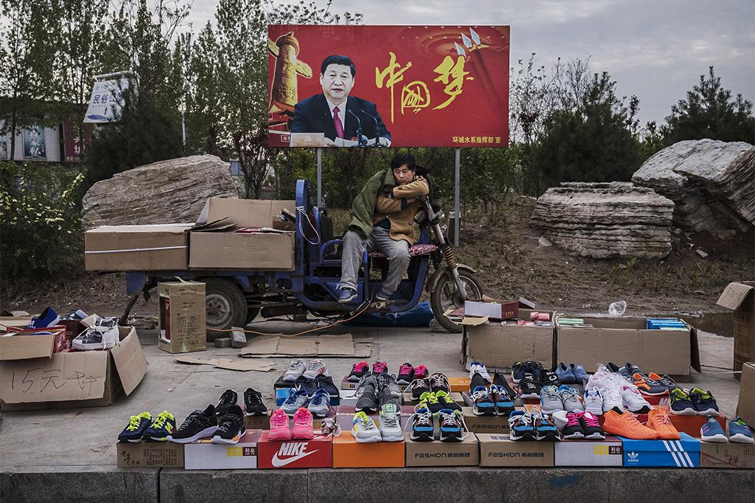 """2017年4月9日石家莊,中國攤販在街頭賣運動鞋,背後為""""中國夢""""的宣傳標語。"""