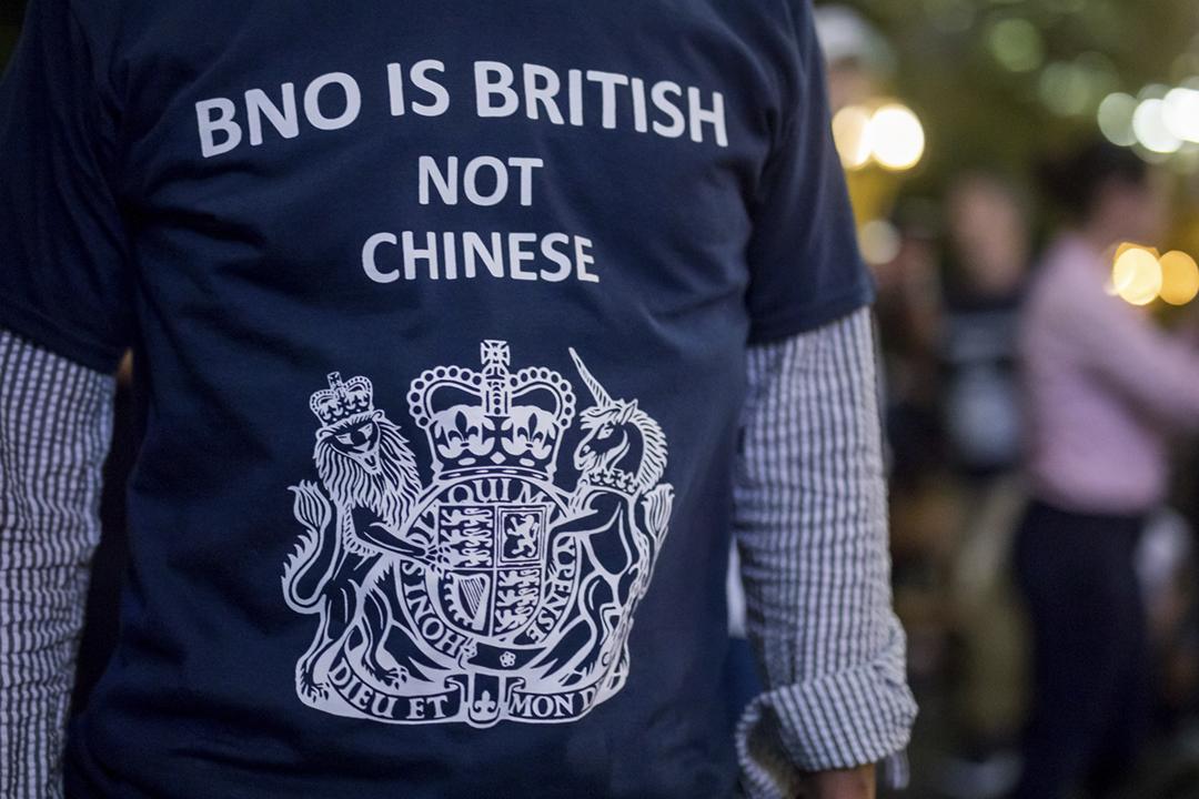 2019年8月16日在香港中環遮打花園,一名示威人士穿上寫有「英國海外國民是英國公民,而非中國人」標語的 T 恤。 攝:Paul Yeung / Bloomberg via Getty Images