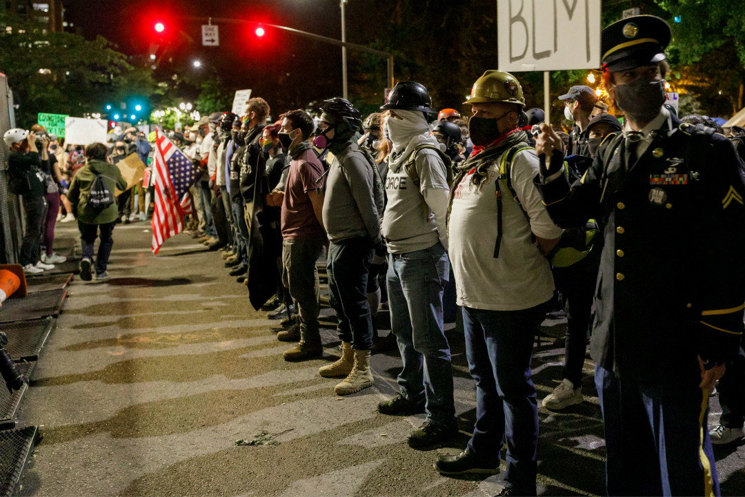 2020年7月24日,美國波特蘭市,退伍老兵在法院大樓前站成一排,與各行業者一起抗議特朗普政府派遣聯邦部隊進入該市。 攝:John Rudoff/Getty Images