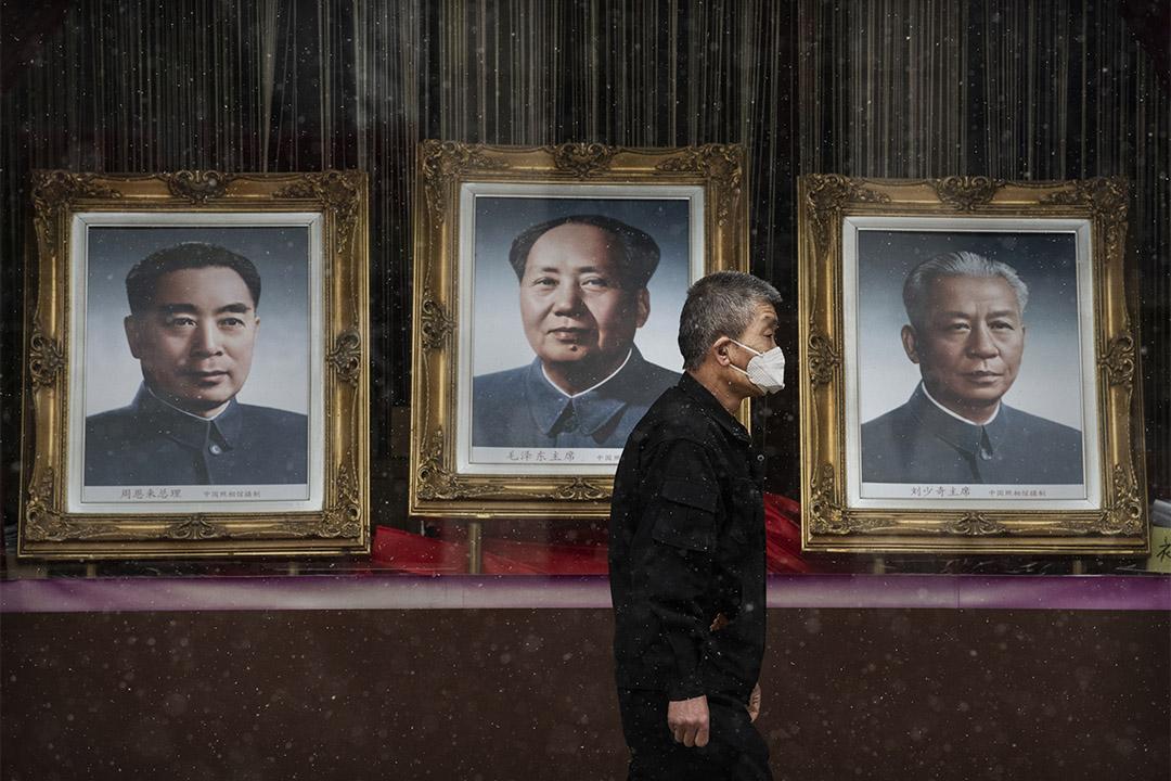 2020年2月14日北京,一個中國男子戴著口罩走過已故中國領導人毛澤東主席的照片。