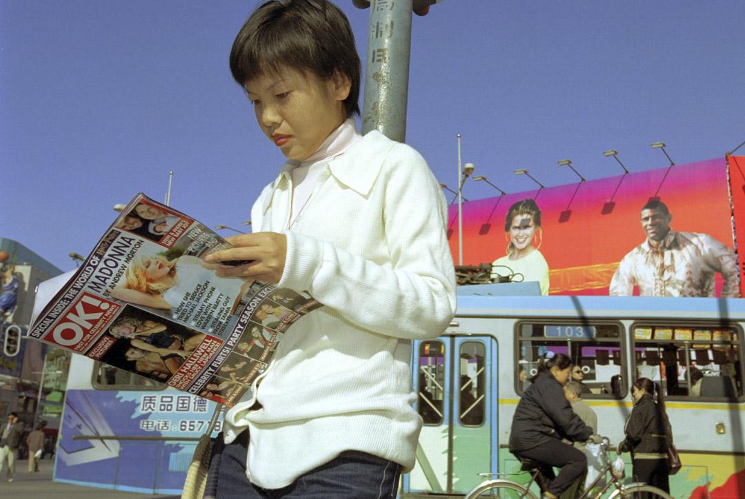 2001年11月11日,在中國正式獲准加入世界貿易組織後的第二天早上,一名婦女在北京市中心讀一本西方名人雜誌。