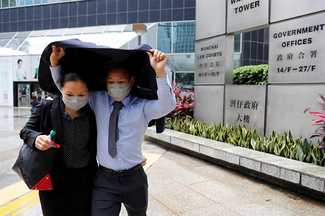 2020年3月3日,湯偉雄和杜依蘭於上法庭聆訊時,以衣服擋雨。