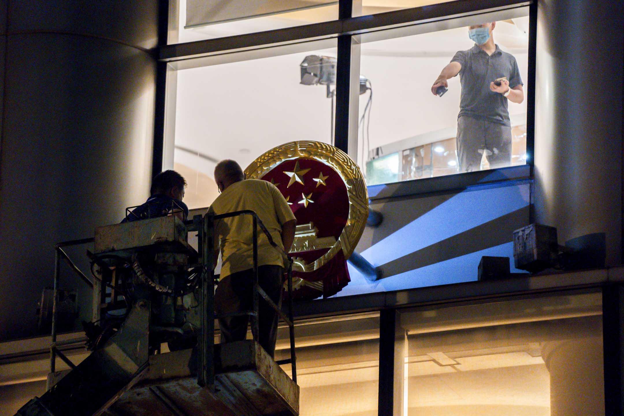 2020年7月7日凌晨,採用銅鑼灣維景酒店一整座作臨時辦公室的駐港國安公署,由工人架起中華人民共和國的國徽。 攝:林振東/端傳媒