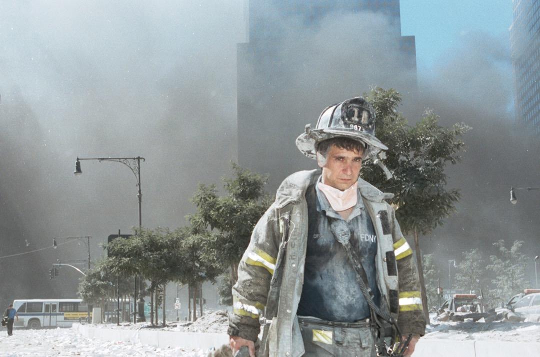 2001年9月11日,美國紐約市,一名當地消防員在倒塌的世貿雙子塔前走過。