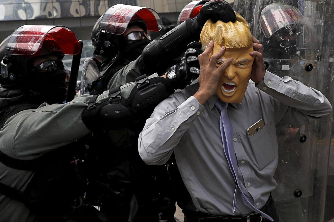 2019年9月29日,銅鑼灣舉行的一個示威中,一名戴著特朗普面具的示威者被防暴警察推開。