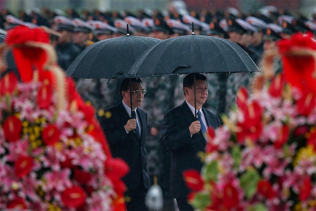 2013年10月1日,中國國家主席習近平(右)和總理李克強(左)在天安門廣場舉行的建國64週年儀式時舉傘。