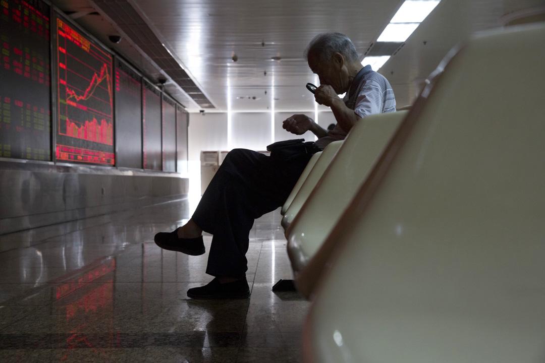 2015年7月9日,中國股民在北京一家經紀公司觀看股票價格時,用放大鏡看著他的手機屏幕。