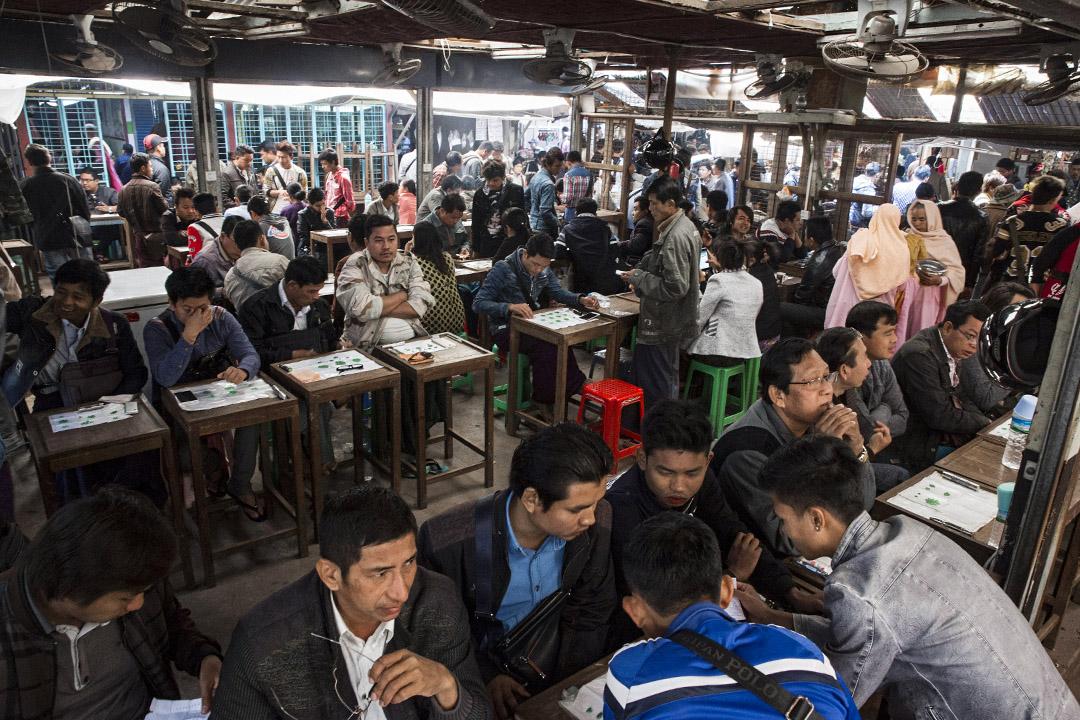 2016年1月30日緬甸,玉石商人在緬甸的曼德勒玉器市場與顧客坐在小桌交易。