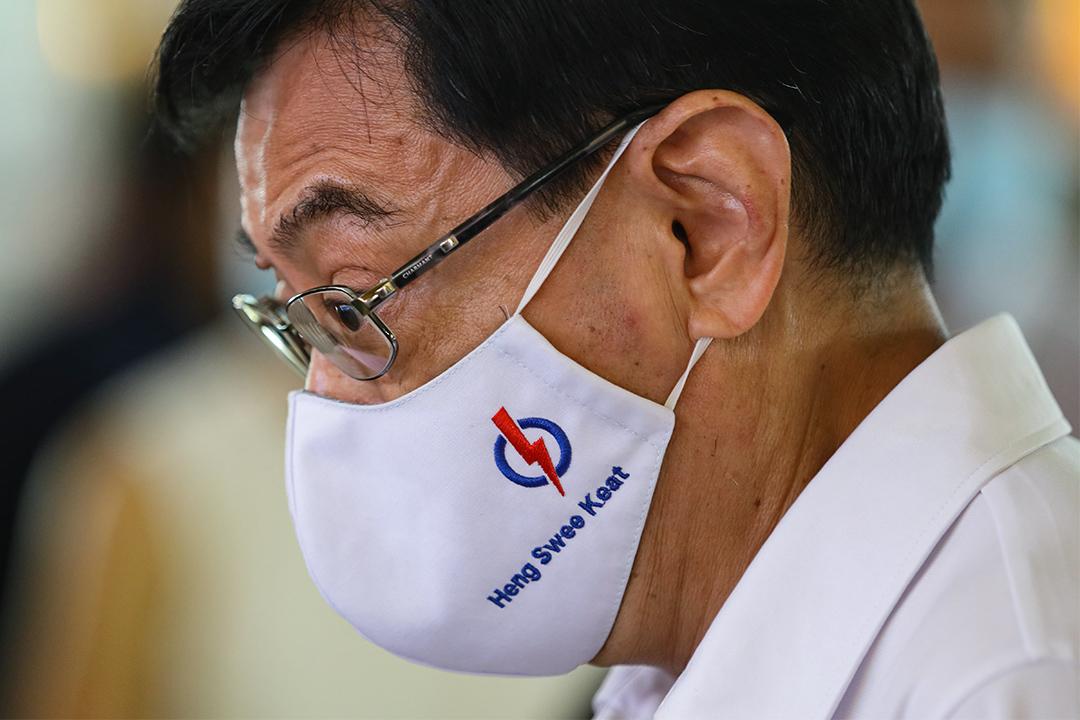 2020年7月8日新加坡,人民行動黨候選人和新加坡副總理王瑞傑在大選前的競選活動中戴上繡有他的名字和黨的標誌的口罩。