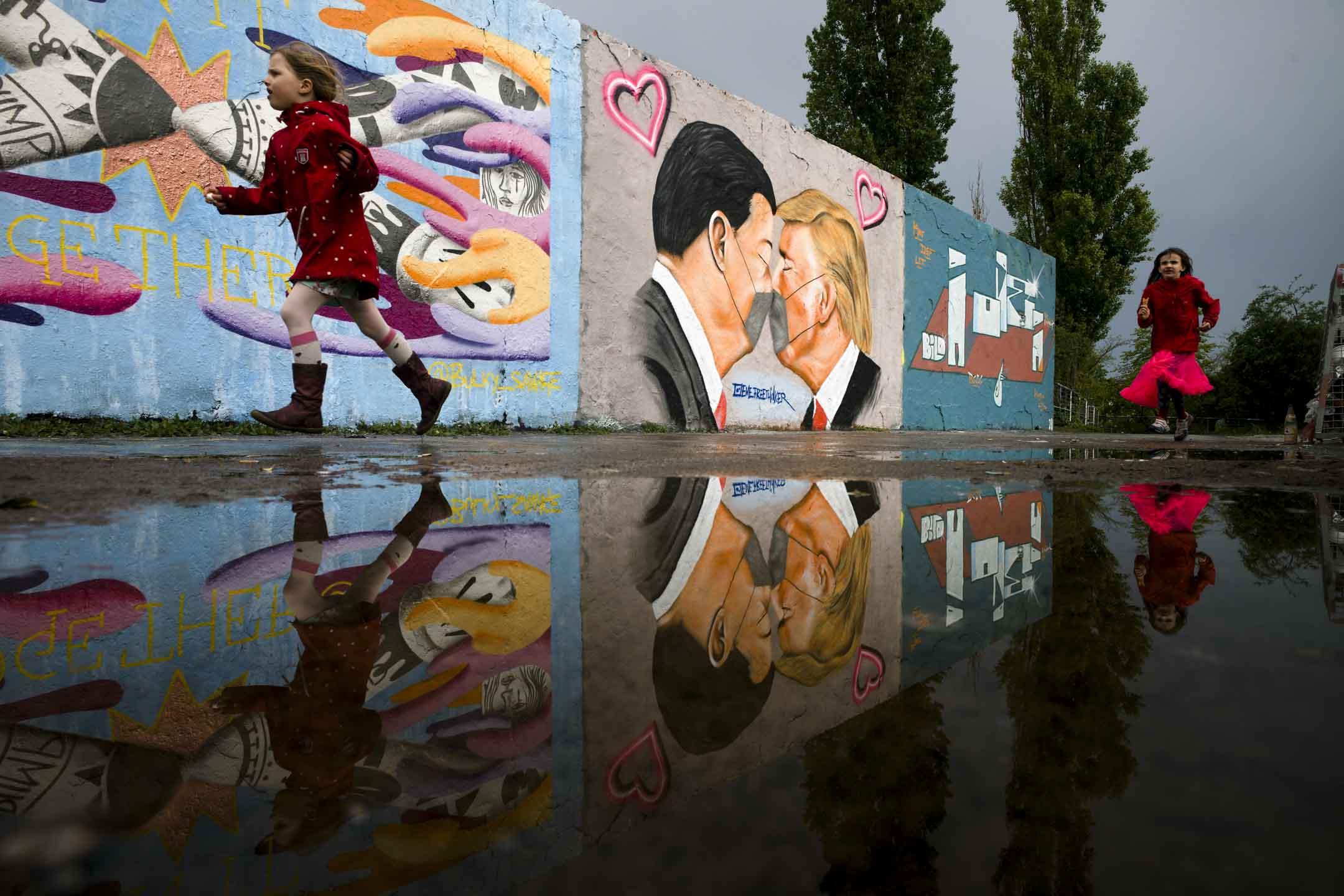 2020年4月29日,德國柏林Mauerpark公園的牆上有塗鴉描繪美國總統特朗普和中國國家主席習近平隔著口罩互相親吻。 攝:Markus Schreiber/AP/達志影像