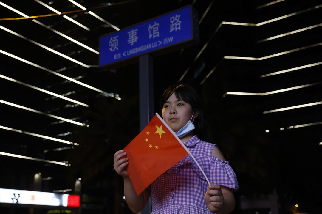 2020年7月26日,一個孩子拿著中國國旗,在美國駐成都領事館附近擺姿勢拍照。