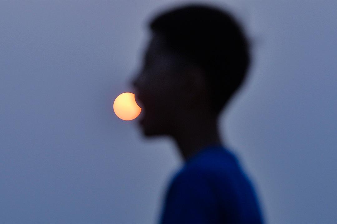 2018年8月11日中國山東省,隨着太陽落下,孩子與日食合影。
