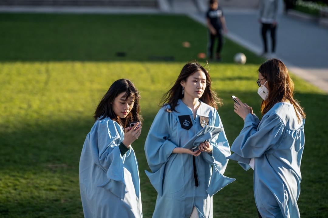 2020年4月28日,美國紐約市哥倫比亞大學,有畢業生帶著口罩拍畢業照。 攝:Alexi Rosenfeld/Getty Images