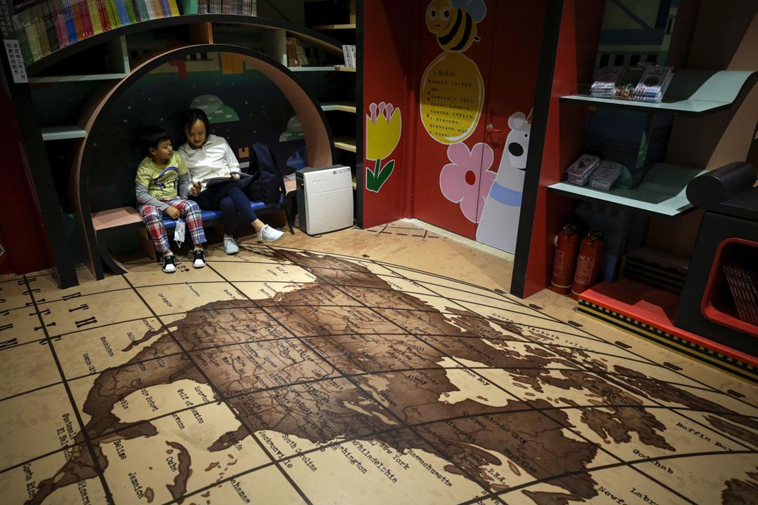 2020年5月17日,一名女士和一名兒童在北京一家書店看書,店內地面有的一張地圖顯示著北美和中美洲。