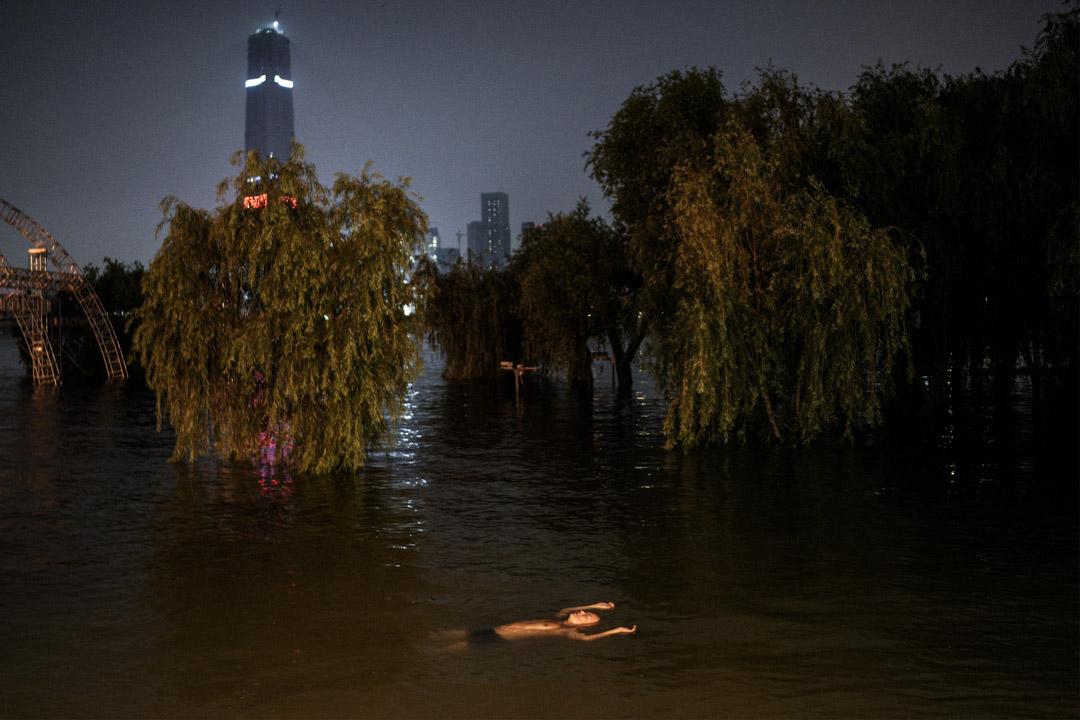 2020年7月9日,湖北武漢,居民在一個被洪水淹沒的公園游泳。