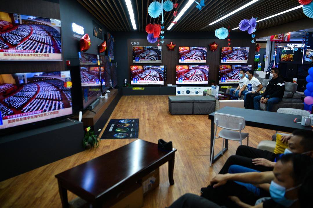 2020年5月22日雲南昆明,人們戴著口罩於蘇寧電器商店的電視屏幕上觀看十三屆全國人大三次會議開幕式的轉播。  攝:Liu Ranyang/China News Service via Getty Images