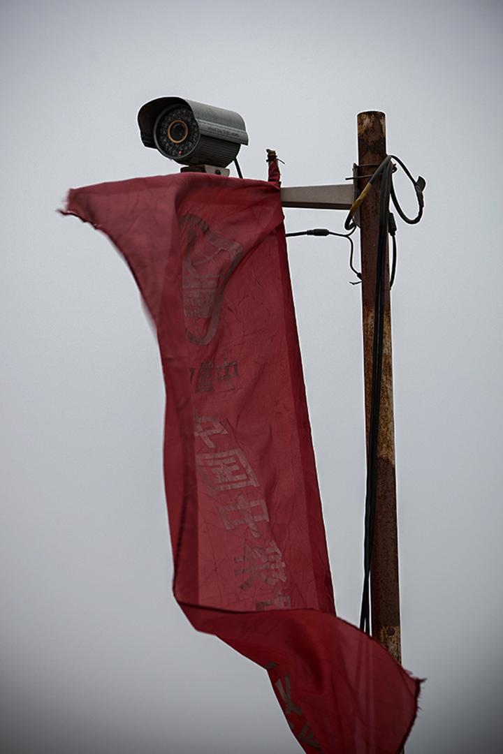 一台閉路監視器前,一面風中飄揚的紅旗在北京朝陽區。