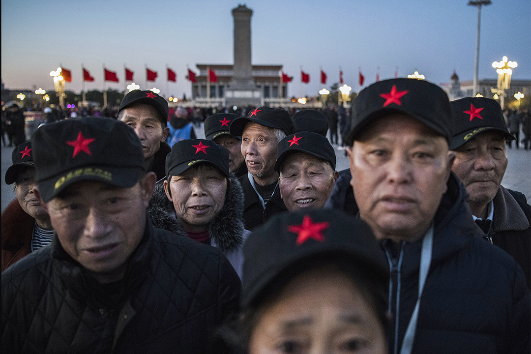 2019年3月15日北京,戴著紅星帽子的中國訪客在天安門廣場等待每日昇旗儀式。