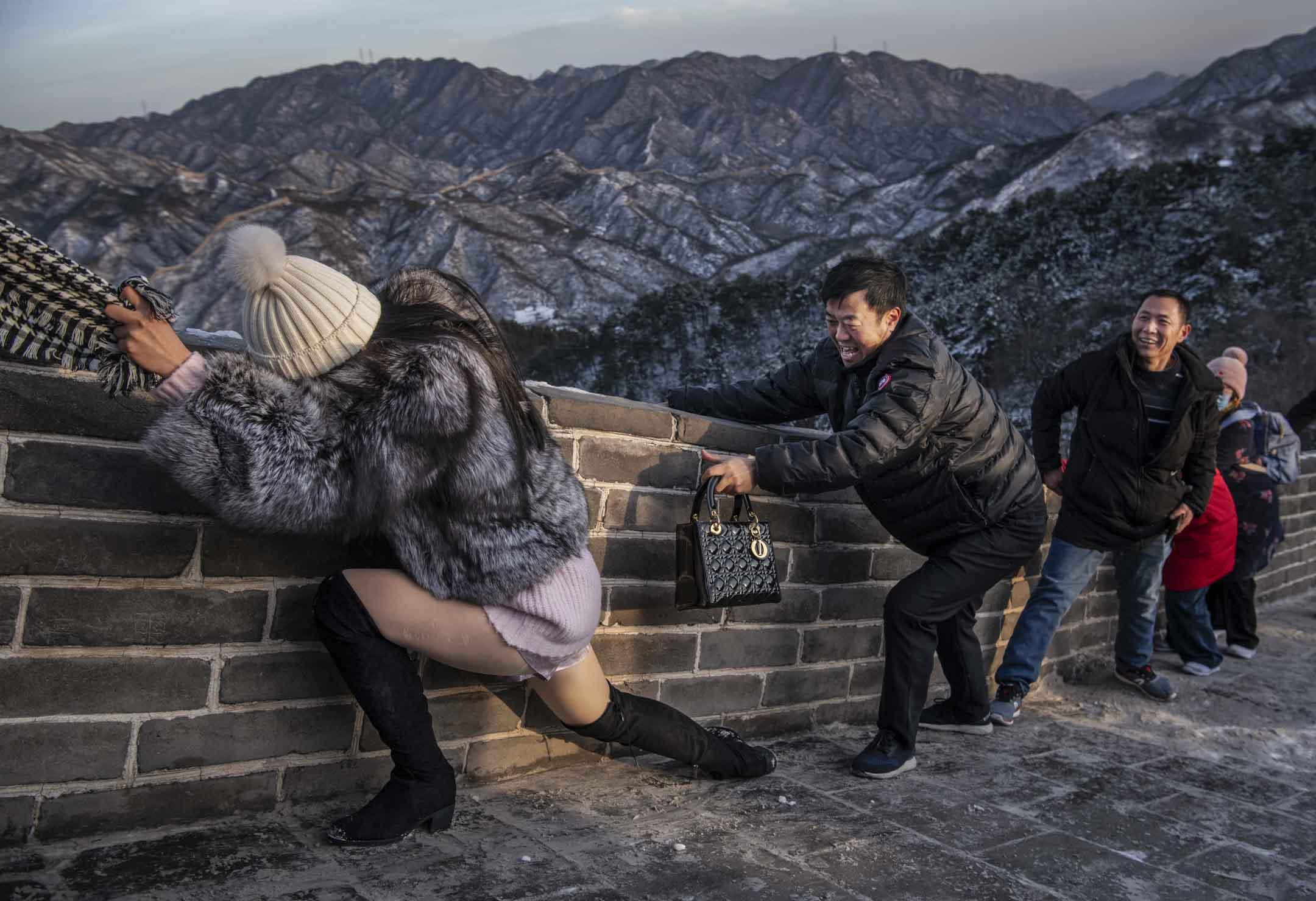 2019年11月30日,北京降雪後的一個寒冷的日子,八達嶺長城上有中國遊客們努力在風中攀爬 。 攝:Kevin Frayer/Getty Images