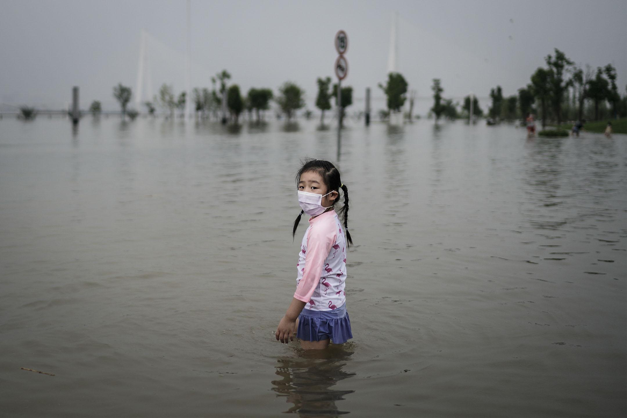 2020年7月10日,武漢江灘公園被洪水淹沒,一位小女孩在水中。 圖: Getty Images