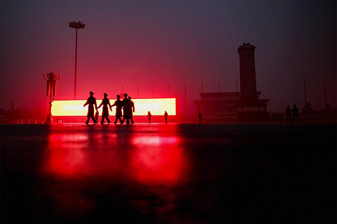 2011年12月5日在北京,中國軍警在霧中經過天安門廣場的一個LED屏幕。 攝:Feng Li/Getty Images