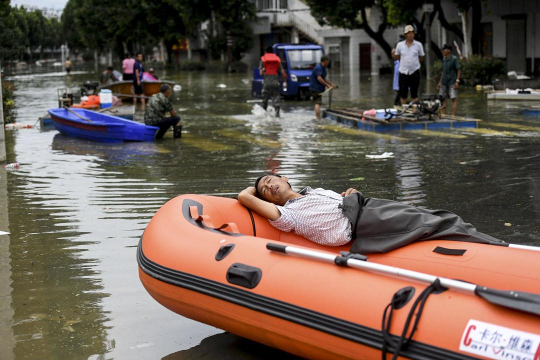 2020年7月23日,巢湖柘皋鎮的洪水下,一位男人在充氣船上休息。