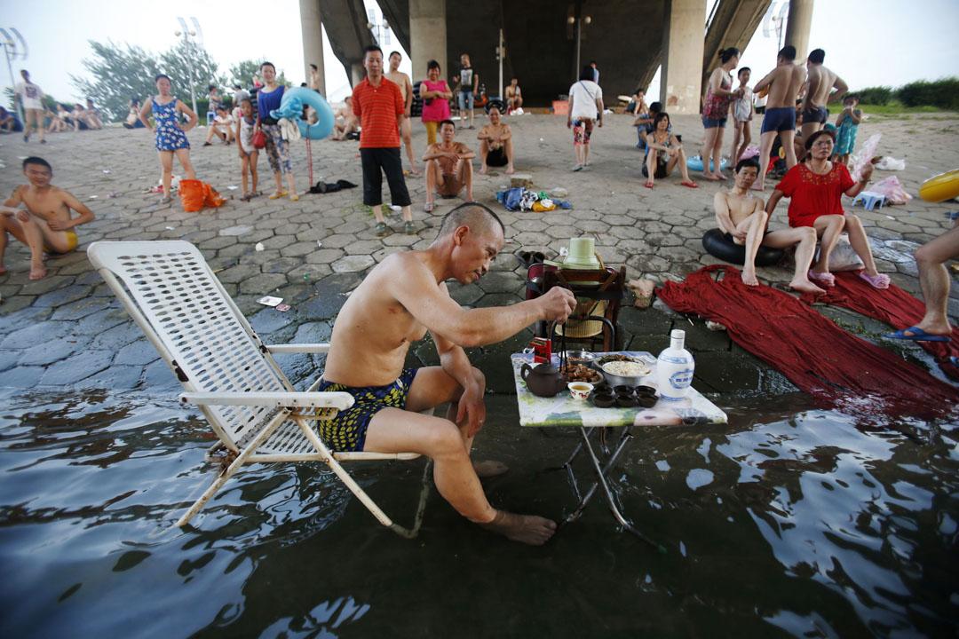 2013年7月28日,高温中的武漢,橋下有男子坐在沙灘椅上吃飯。