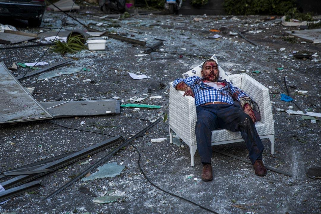 一名受傷男子在爆炸現場遺下的椅子上坐下休息。