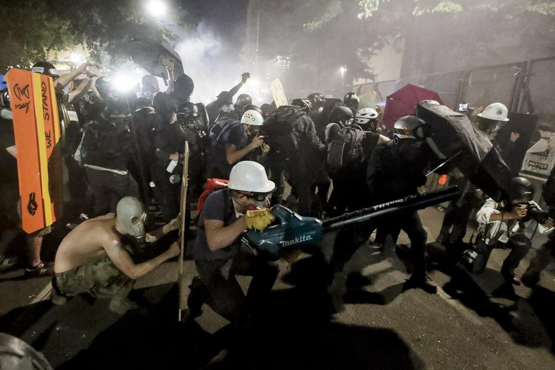 2020年7月29日,波特蘭示威者用傘、木板、吹風機等應對防暴警察發射的催淚彈。