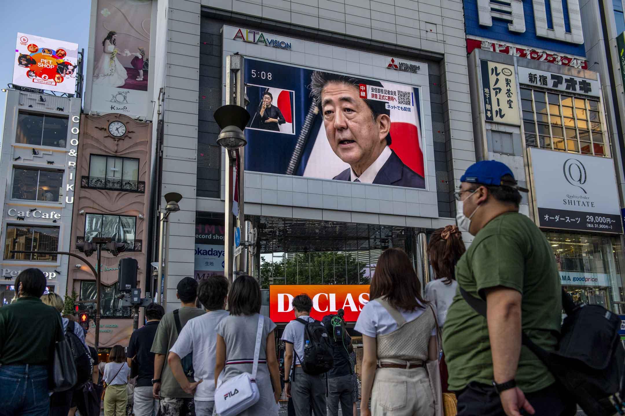 2020年8月28日,日本首相安倍晉三在巨大的電視屏幕上,他在記者會宣布辭職。 攝:Carl Court/Getty Images