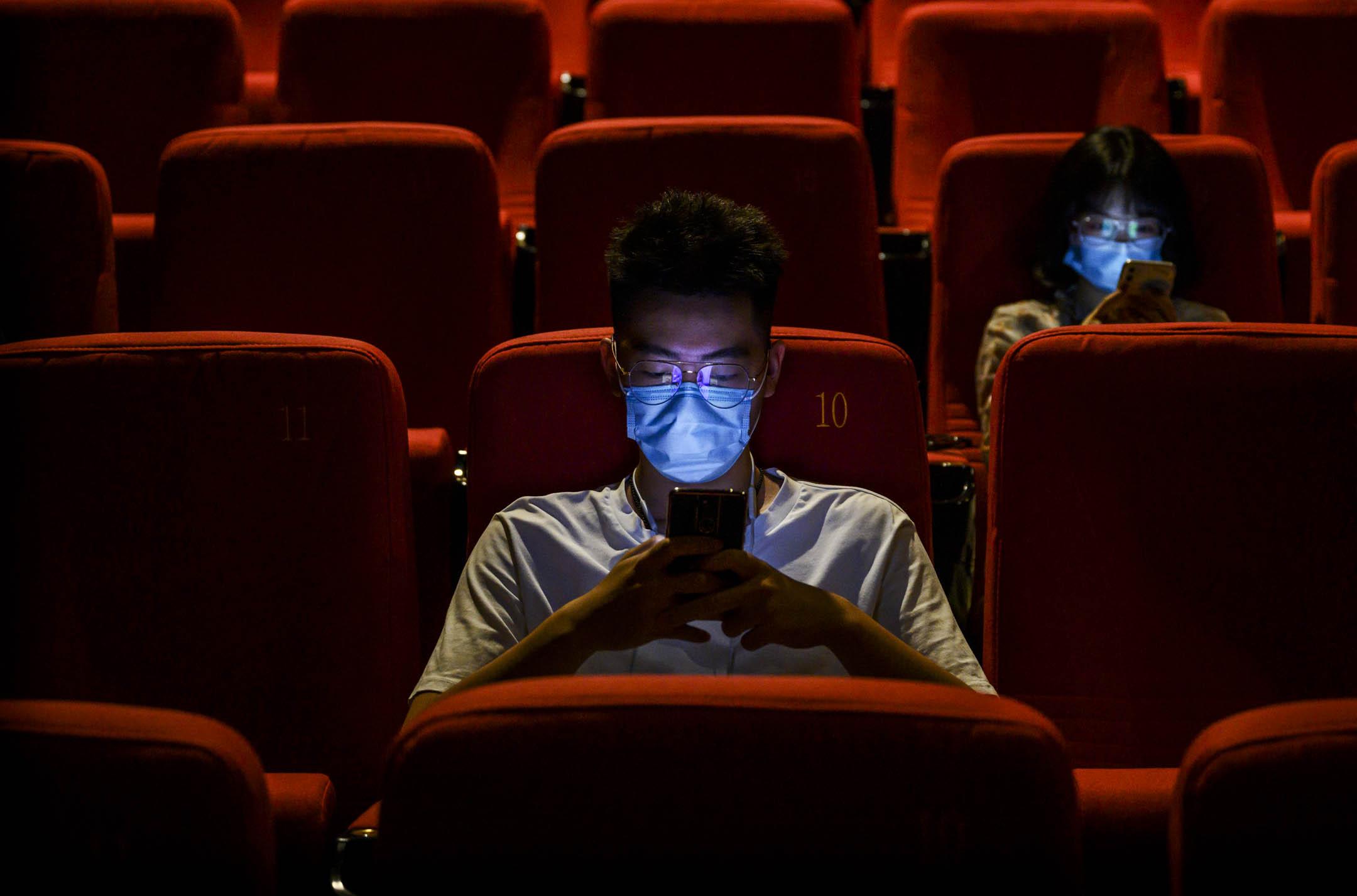 2020年7月24日,北京,戴著口罩人們在電影放映前觀看智能手機。