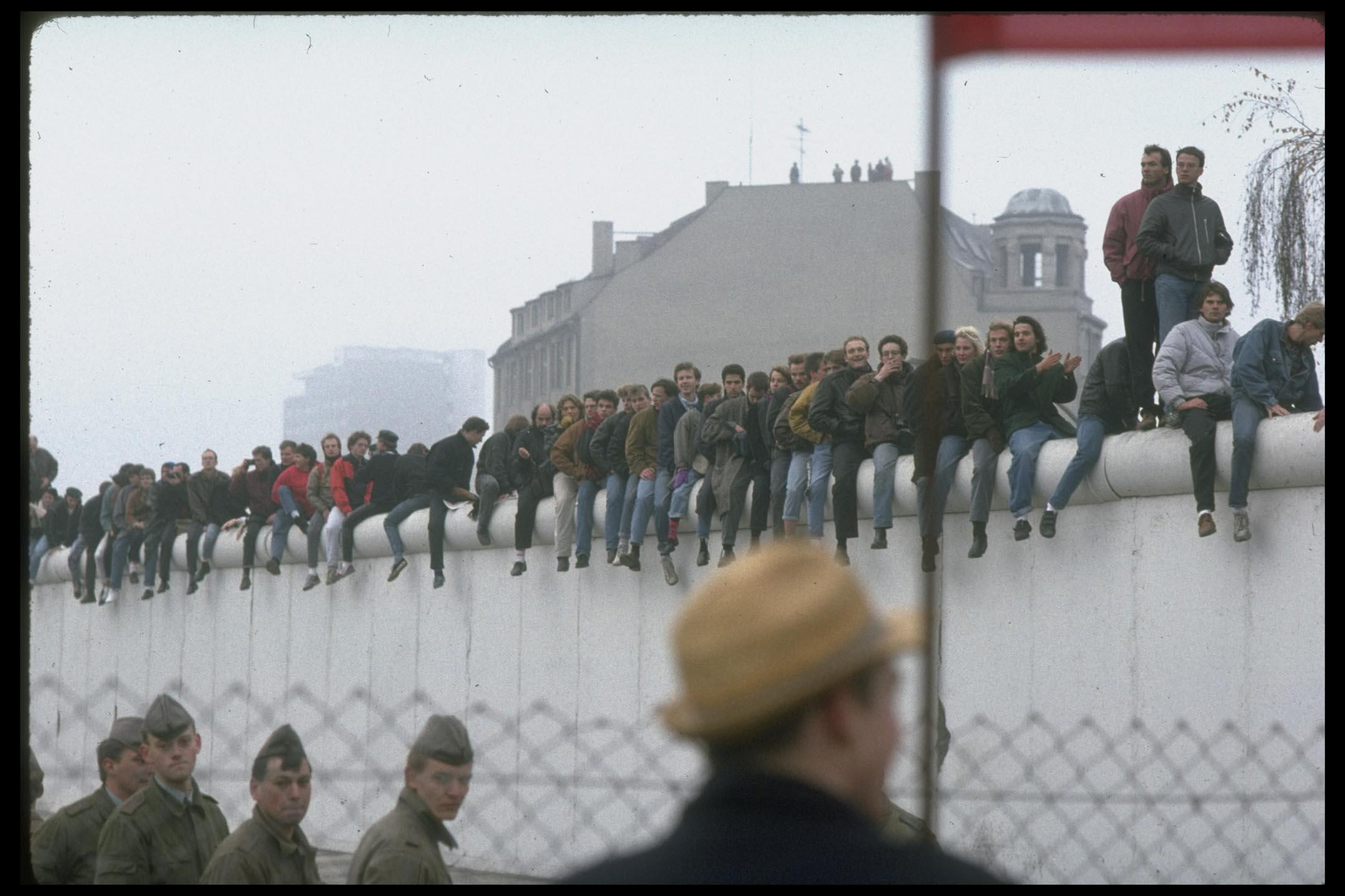 東柏林人坐在柏林圍牆上。