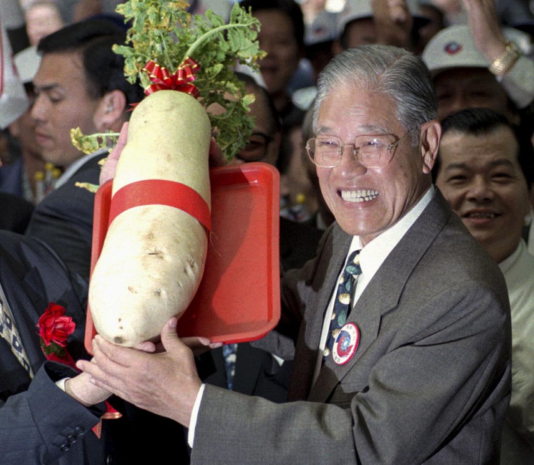 1996年2月17日,時任台灣總統李登輝出席活動時,舉起一個大蘿蔔,象徵著好運。 攝:Eddie Shih/AP/達志影像