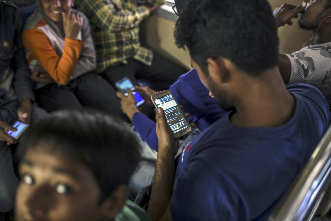 2020年2月15日,乘客在印度孟買火車站月台使用智能手機。
