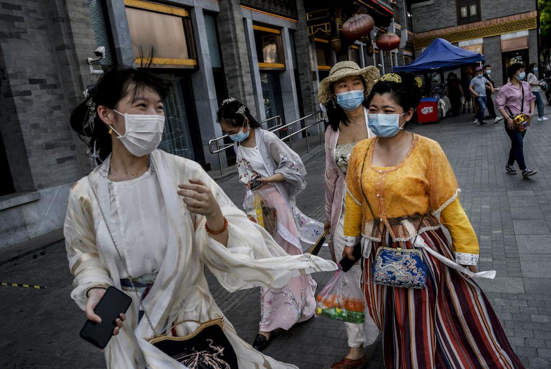2020年5月2日,北京,女士們在街道上行走,穿著傳統服裝和口罩。