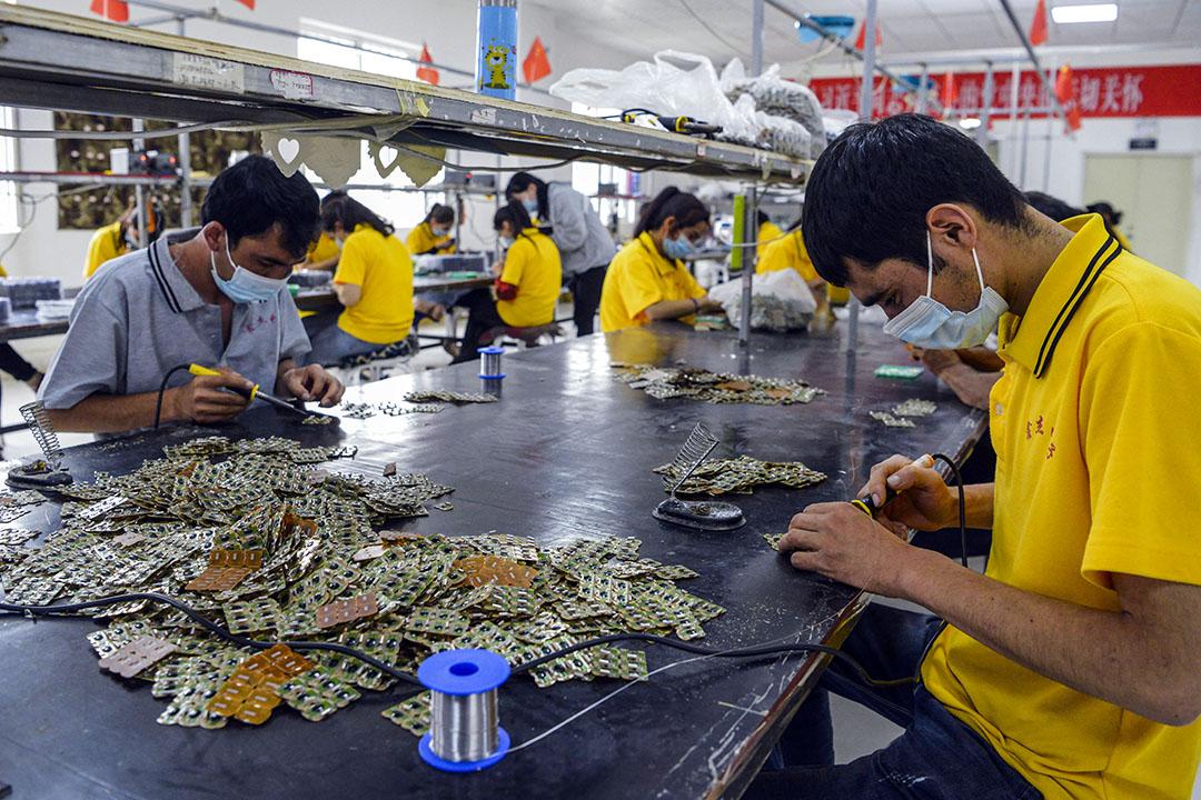 2020年6月18日中國新疆維吾爾自治區,工人在一家電子工廠裏戴着口罩工作。
