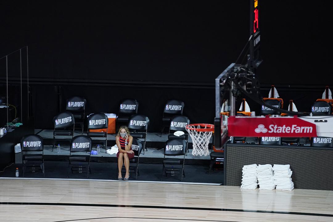 2020年8月26日在美國佛羅里達州,由奧蘭多魔術(Orlando Magic)對密爾沃基公鹿(Milwaukee Bucks)的 NBA 季後賽因公鹿球員罷賽而押後,一名記者坐在空無一人的球場邊。 攝:Ashley Landis-Pool / Getty Images