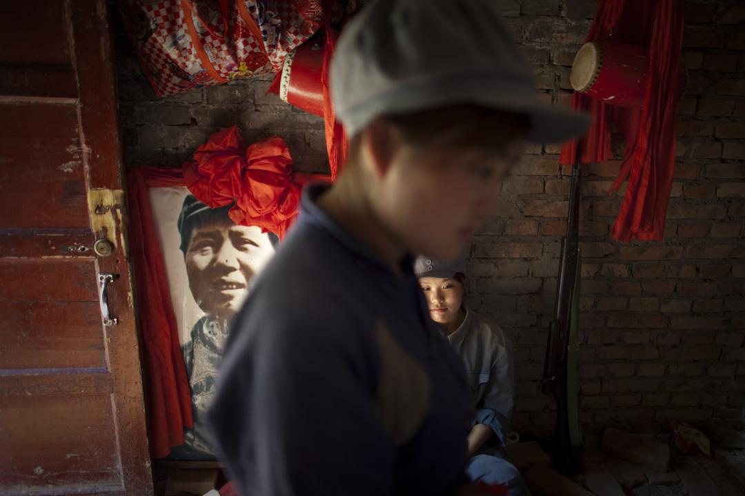 2011年6月29日,延安的一個旅遊景點,扮成紅軍士兵的女演員站在毛澤東的照片旁邊。 攝:Alexander F. Yuan/AP/達志影像