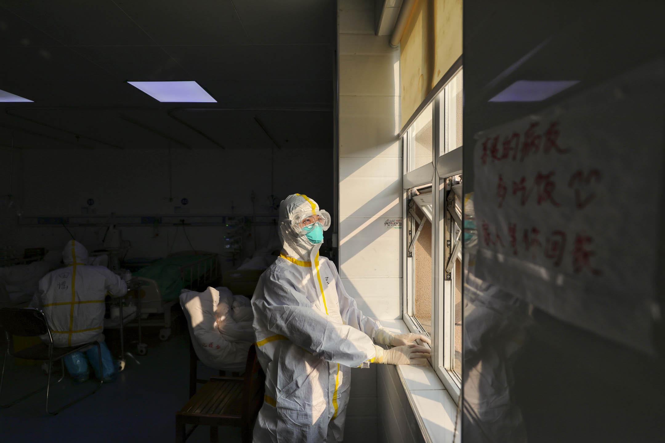 2020年3月12日,一名醫護人員在武漢一所曾經專門治療新冠肺炎患者的醫院向窗外望。 攝:Feature China/Barcroft Media via Getty Images